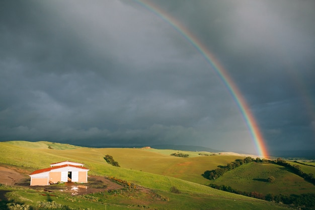 Bright rainbow and green hills with small house on dark cloudy sky background