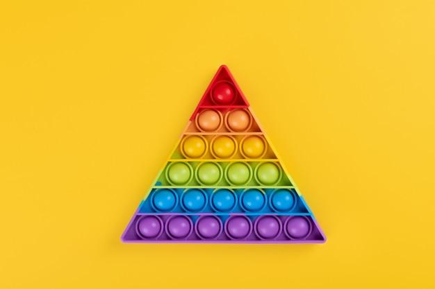 노란색 배경에 있는 어린이와 성인을 위한 밝은 무지개 장난감 안티 스트레스