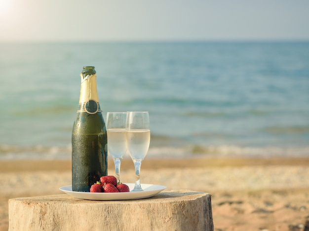 Bright rays of the sun illuminate the bottle of champagne on the beach.