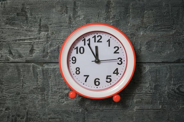 Ярко-красный будильник на деревянных фоне. классические аналоговые часы.
