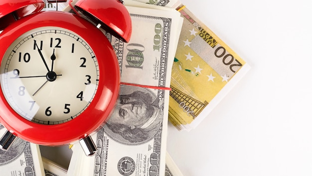 Bright red alarm clock in retro style on a pile of paper dollars and euros. time is money. business concept.