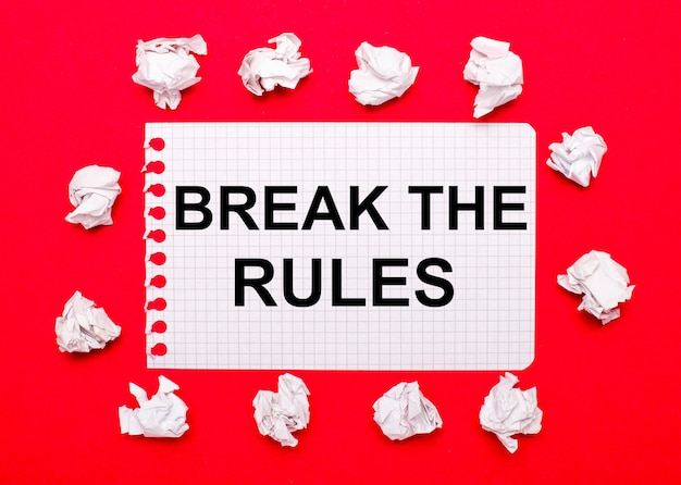 On a bright red background, white crumpled sheets of paper and a sheet of paper with the text break the rules