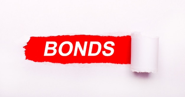 On a bright red background, white paper with a torn stripe and the inscription bonds.