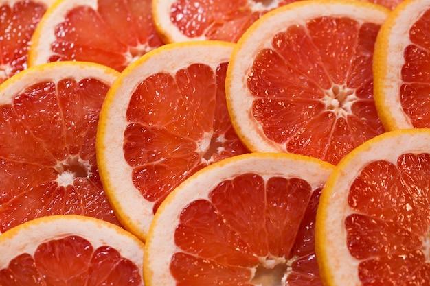グレープフルーツのジューシーなスライスと真っ赤な背景。健康食品の背景。