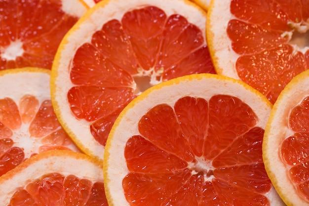 グレープフルーツのジューシーなスライスと真っ赤な背景。