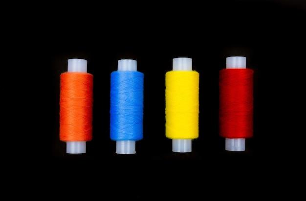 Ярко-красные, синие, желтые, розовые мотки ниток для пришивания на черном фоне.