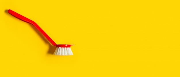 Bright red brush lies on a bright yellow background. top view. copyspace.