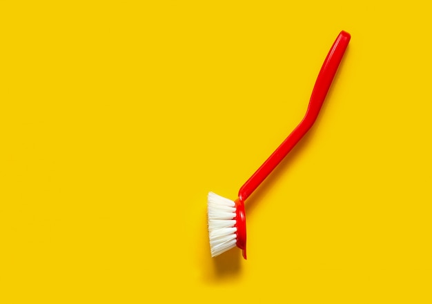 Bright red brush lies on a bright yellow background
