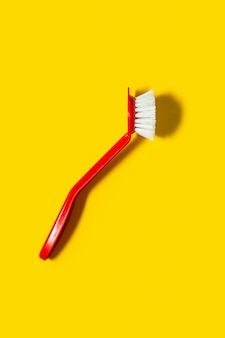 Bright red brush lies on a bright yellow. in the style of pop art. top view