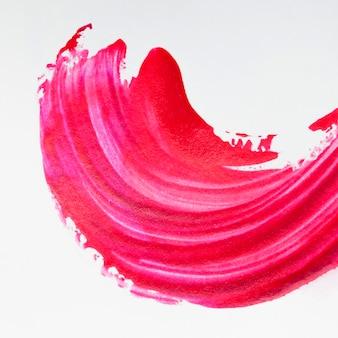 Ярко-красный мазок кисти на белом фоне