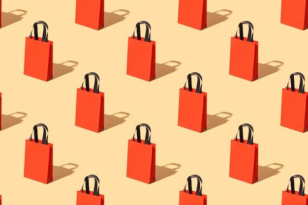 Ярко-красная крафтовая сумка с черными узорчатыми ручками на бежевом фоне. концепция черной пятницы. большая распродажа