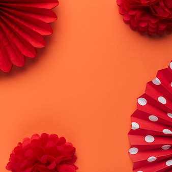 Bright red decorative fake flower and paper fan on orange backdrop
