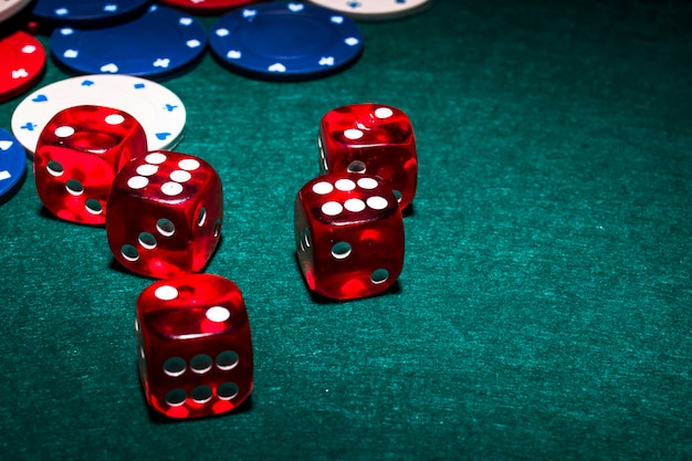 Яркие красные кубики на зеленом покерном столе