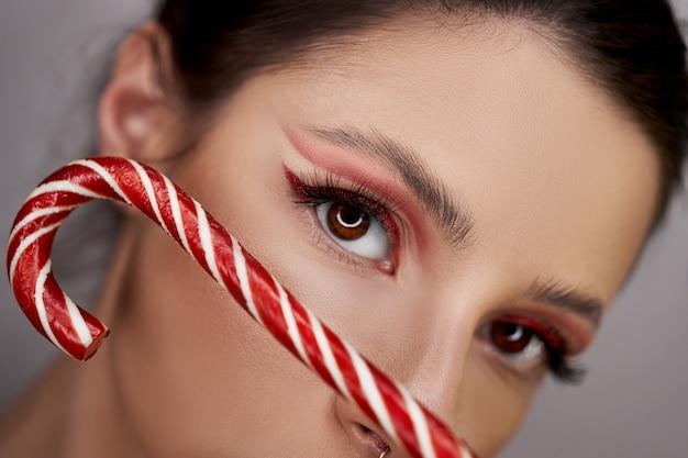 キャラメルを手にした真っ赤なアイメイクの女性のクローズアップ、美しい眉毛と長いまつげ