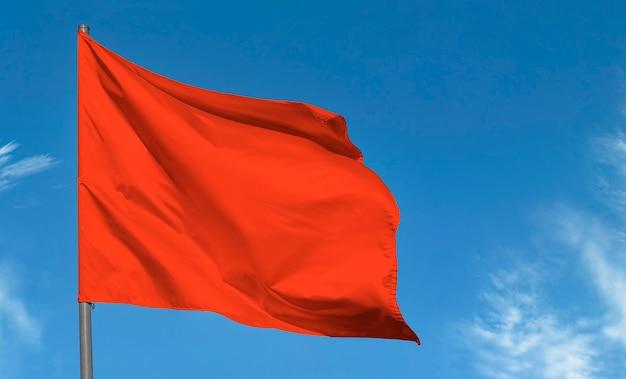 푸른 하늘에 대 한 물결 치는 밝은 붉은 깃발