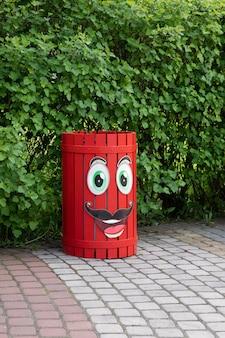 Ярко-красный мусорный бак на улице с мультяшными глазами и ртами понятие экологии