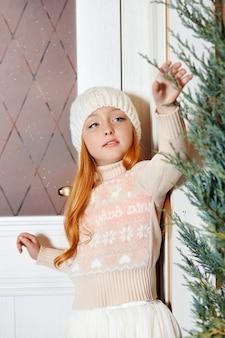 Яркая рыжая девочка в белой шляпе и красивом платье сидит в осеннем кафе. рыжая девушка с большими голубыми глазами и красивым свитером встречает весну