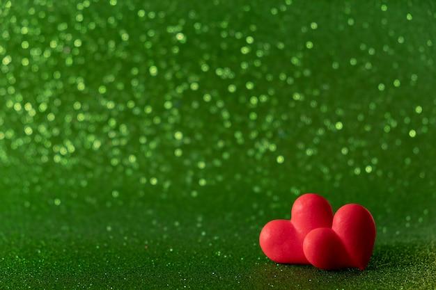 明るい赤の心は、背景の緑のボケ味を抽象化します。バレンタインデーのテクスチャです。