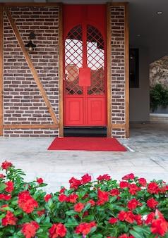 トルコの家のレンガの壁に赤い花に囲まれた真っ赤な鉄の扉