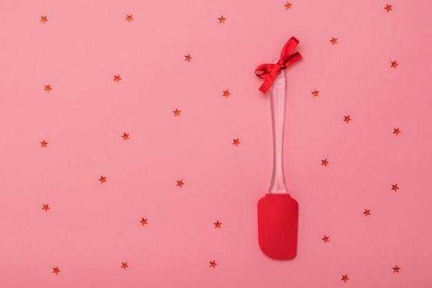星とピンクの背景に赤いリボンで飾られた真っ赤なキッチンヘラ。お祝いの背景にキッチンツール。フラットレイ。