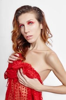 여자의 얼굴에 밝은 빨간색 메이크업, 피부 관리를위한 전문 천연 화장품. 밝은 빨간 눈 화장, 아름다운 눈썹. 흰색 바탕에 젖은 머리를 가진 여자