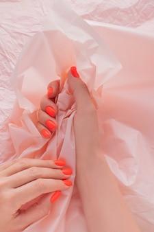 Ярко-красный дизайн маникюра. руки на фоне мятой бумаги.