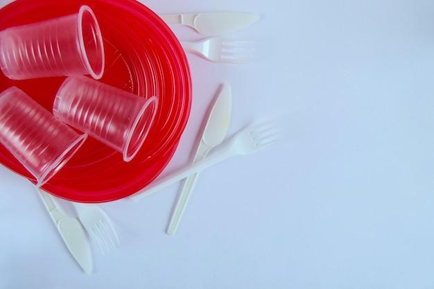 白い表面のクローズアップに真っ赤なプラスチック製の使い捨て食器