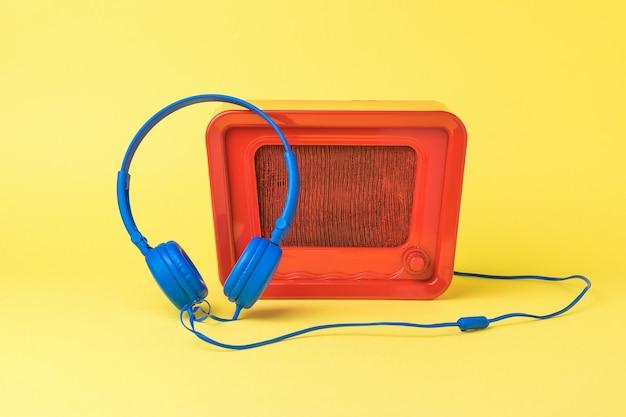 밝은 빨간색 복고풍 라디오 및 노란색 배경에 파란색 헤드폰. 사운드 및 비디오 재생 기술.
