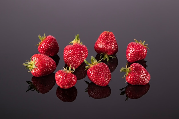 Bright red ripe strawberries on a black mirror table delicious and healthy berries