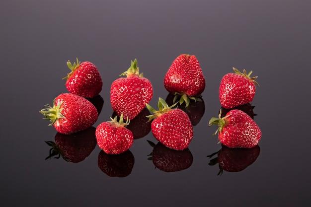 디저트 샐러드 또는 스무디를 위한 검은 거울 테이블 재료에 밝은 빨간색 익은 딸기