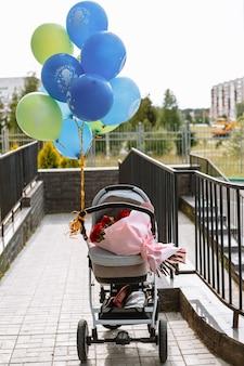 Яркие красные розы, лежащие в детской коляске с воздушными шарами