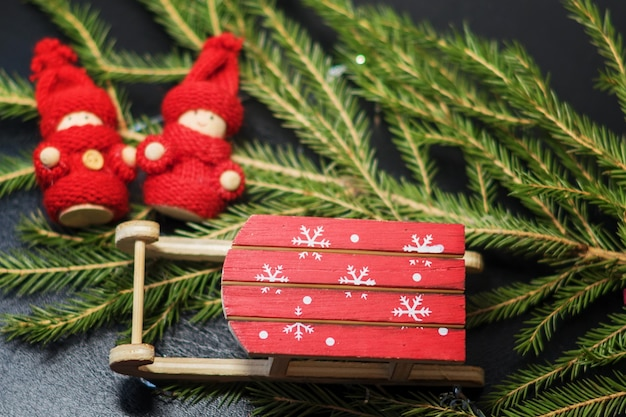 Ярко-красные сани санты со снежинками с елкой и деревянным младенцем в ярко-красной вязаной одежде.