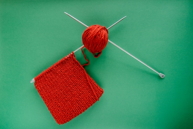 Bright red scarf with knitting needles. on green background. green and red contrast.