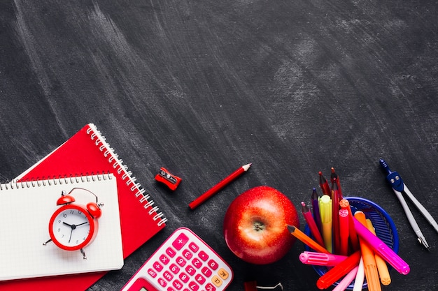 Bright red school supplies and apple on chalkboard