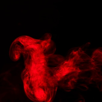 Bright red smoke fumes on black background