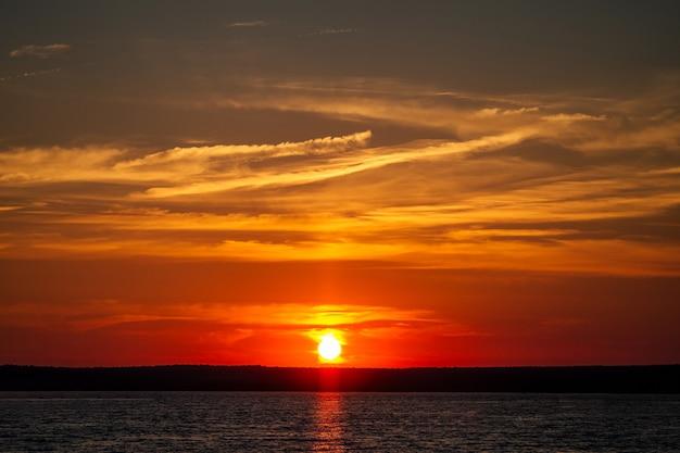 Ярко-красный закат на реке с облаками