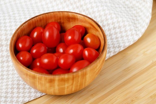 木製のカップに入った真っ赤なトマトキッチンで調理する準備ができました