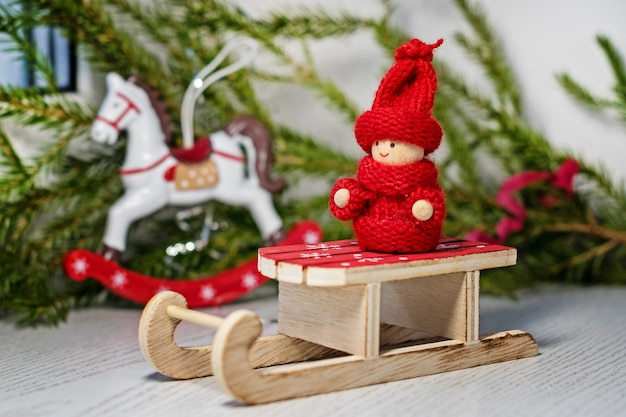 Ярко-красный игрушечный малыш в вязаной одежде на санях санты с елкой и игрушечной лошадкой.