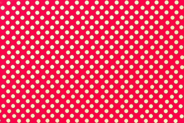 Bright red wrapping paper with a pattern of golden polka dot closeup.