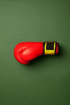 Bright red and yellow boxing glove. professional sport equipment isolated on green studio background. concept of sport, activity, movement, healthy lifestyle, wellbeing. modern colors.