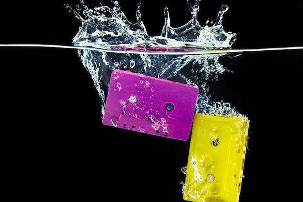 Bright retro audio cassette diving into the water against black background