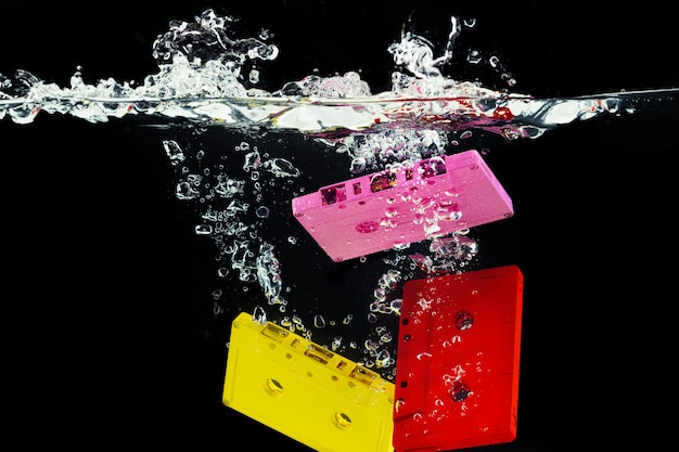 Bright retro audio cassette diving into the water against black  close up