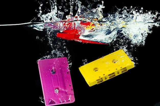 Bright retro audio cassette diving into the water against black wall close up