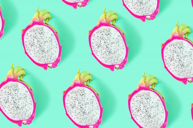 Bright rich background made of sliced dragon fruit or pitahaya on green.