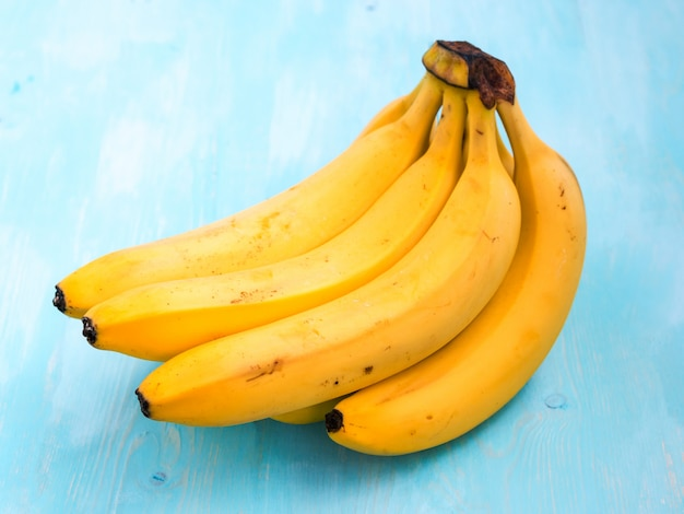 Bright ripe organic bananas on blue wooden table. banch of banana on blue background. copy space for text.