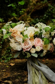 Bright romantic bouquet of flowers with ribbons on a light background