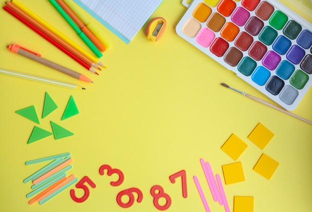 Яркий школьный фон со школьными принадлежностями на желтом, плоской планировке, копией пространства
