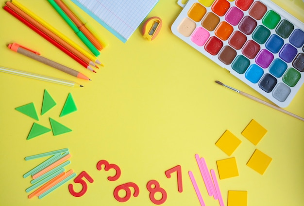 Bright school background with school supplies on yellow, flat lay, copy space