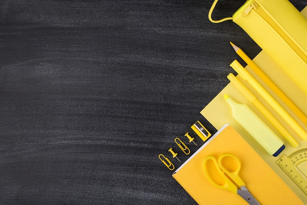 Bright school and office stationery concept. top above overhead view photo of yellow stationery isolated on blackboard with empty blank copyspace
