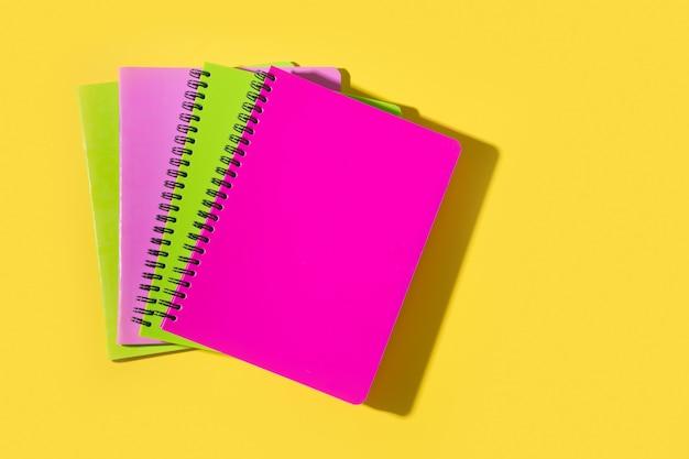 Яркие школьные принадлежности, тетради на желтом. вид сверху, плоская планировка.